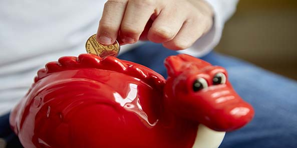 Child saving with a Dylan the dragon money box.
