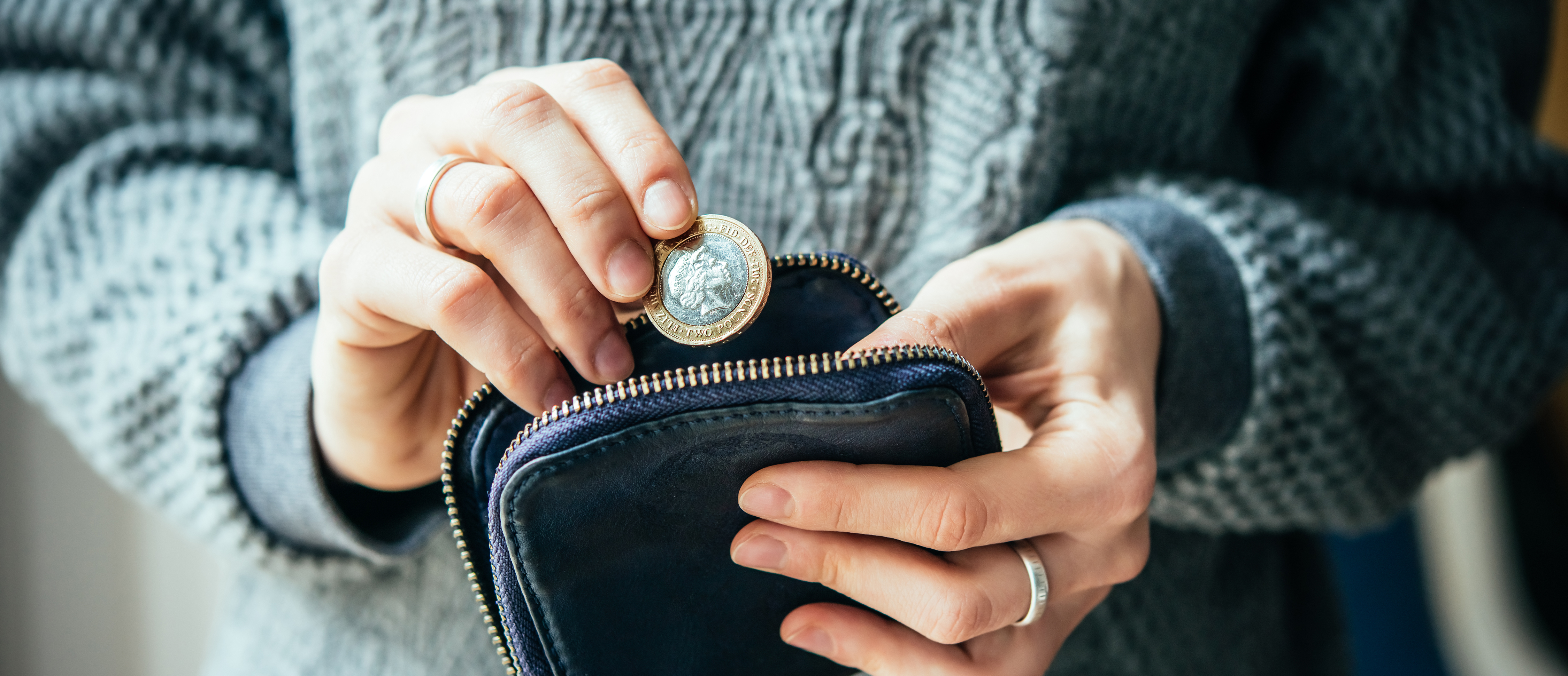 Coin being placed in to purse