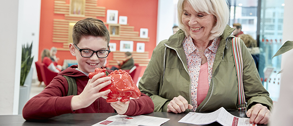 Young boy holding moneybox with grandparent